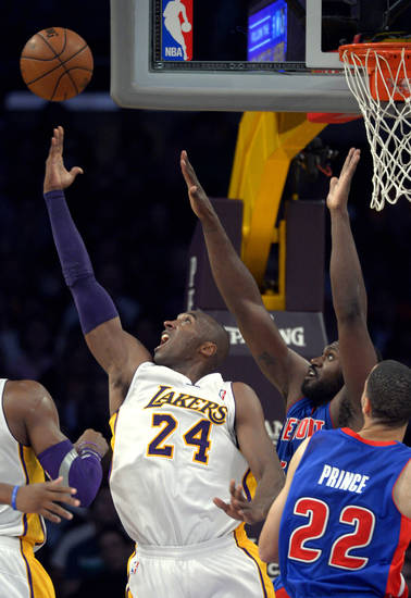 Los Angeles Lakers guard Kobe Bryant, left, puts up a shot as Detroit Pistons forward Jason Maxiell, upper right, defends and forward Tayshaun Prince looks on during the first half of their NBA basketball game, Sunday, Nov. 4, 2012, in Los Angeles. (AP Photo/Mark J. Terrill)