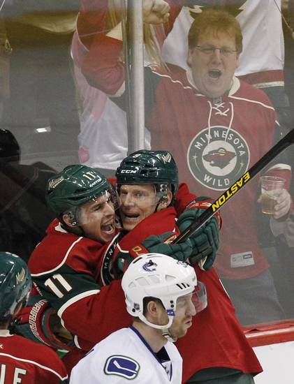Minnesota Wild left wing Zach Parise (11) celebrates scoring a goal with teammate Mikko Koivu, of Finland, who had the assist as Vancouver Canucks right wing Jannik Hansen, of Denmark, reacts during the first period of an NHL hockey game Sunday, March 10, 2013, in St. Paul, Minn. (AP Photo/Genevieve Ross)