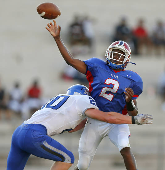 Bridge Creek's Morgan Merrell hits John Marshall's Lenard Levinston as he throws during a high school football game at Taft Stadium in Oklahoma City, Thursday, September 6, 2012. Photo by Bryan Terry, The Oklahoman
