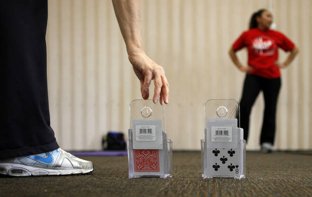 Instructor Robin Barlow reaches for a playing card during a Move Into Fitness class in Moore, Okla., Thursday, March 22, 2012. The cards were used to randomize the exercises in the class. Photo by Bryan Terry, The Oklahoman