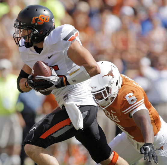 Oklahoma State's Josh Cooper (25) makes a long catch in front of Texas' Christian Scott (6) in the first quarter during a college football game between the Oklahoma State University Cowboys (OSU) and the University of Texas Longhorns (UT) at Darrell K Royal-Texas Memorial Stadium in Austin, Texas, Saturday, Oct. 15, 2011. Photo by Nate Billings, The Oklahoman