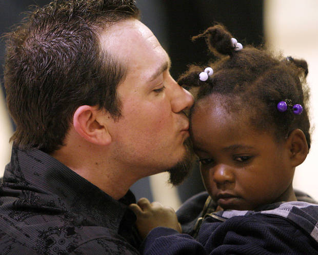 Stephen Lee kisses his newly adopted daughter from Haiti, Biverlie, as they meet at Will Rogers World Airport in Oklahoma City early on Thursday, Jan. 21, 2010. Photo by John Clanton, The Oklahoman
