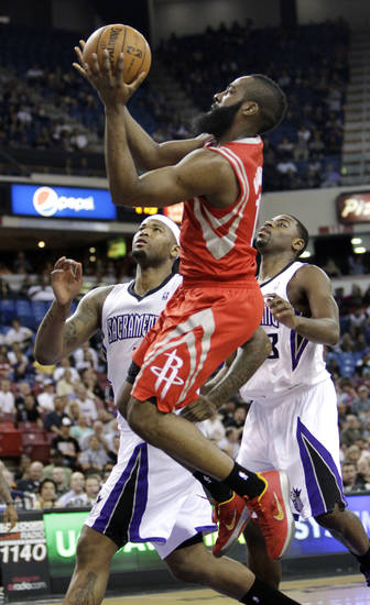 Houston Rockets guard James Harden, center, shoots between Sacramento Kings' DeMarcus Cousins, left, and Tyreke Evans during the first quarter of an NBA basketball game in Sacramento, Calif., Wednesday, April 3, 2013. (AP Photo/Rich Pedroncelli)