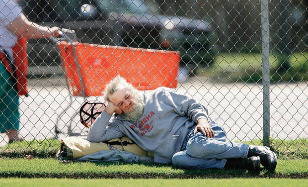 David, who said he lives on the streets, sleeps against a fence near SW 4 and Harvey as a woman pushes a cart full of trash near the parking lot at The Salvation Army offices. PHOTOS BY Jim Beckel, The Oklahoman