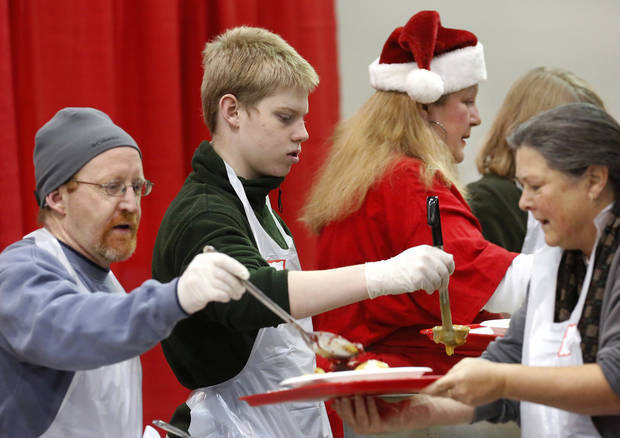 Volunteers in the serving line put food on guests' plates. From left are Jim Scheihing of Edmond and his son, Dylan, and Hellen Kellar, The Scheihings came as a family, making their first visit to volunteer at the Red Andrews Dinner. Jim and his wife, Kari, were accompanied by their three children, Dylan, Jake and Carly. Kari Scheihing said they would celebrate the Christmas holiday as a family in their home later in the day. It was Kellar's first time to volunteer, too. Hundreds were served a traditional Christmas meal at the annual Red Andrews Dinner inside the Cox Convention Center on Christmas Day, Dec. 25, 2012. An army of  volunteers showed up despite  snow and ice and hazardous driving conditions. They accompanied each guest through the serving line and carried their trays and seated them at their tables. Other volunteers distributed a small mountain of toys and stuffed animals that were donated for the event.   Photo by Jim Beckel, The Oklahoman