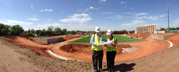 Gary L. Armbruster, Principal Architect, and Marsha Gallant of MA+ Architecture, look over plans to rebuild Taft Stadium in this provided photo taken in May, shortly after the new artificial turf playing surface was installed at the stadium. Taft won't be ready for high school football until the fall of 2015, but could again become a potential site for state championship games in the future.