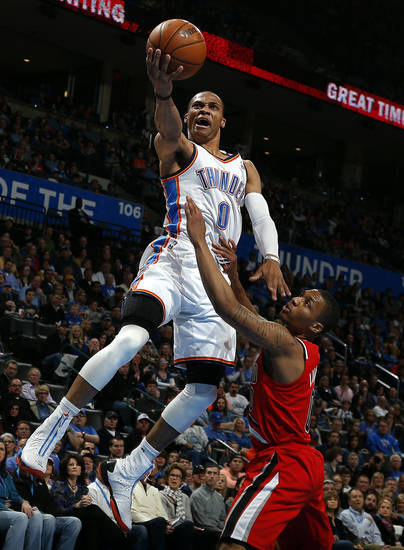 Oklahoma City's Russell Westbrook (0) shoots a lay up as Portland's Damian Lillard (0) defends during the NBA basketball game between the Oklahoma City Thunder and the Portland Trail Blazers at the Chesapeake Energy Arena in Oklahoma City, Sunday, March, 24, 2013. Photo by Sarah Phipps, The Oklahoman