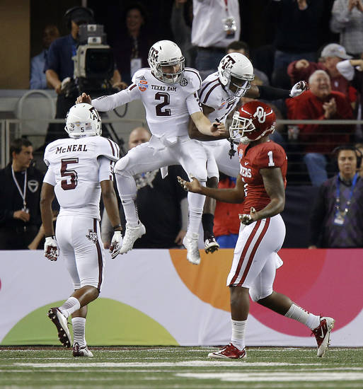 Texas A&M 's Johnny Manziel (2) and Texas A&M 's Uzoma Nwachukwu (7) celebrate after a touchdown in front of Oklahoma's Tony Jefferson (1) during the Cotton Bowl college football game between the University of Oklahoma (OU)and Texas A&M University at Cowboys Stadium in Arlington, Texas, Friday, Jan. 4, 2013. Photo by Bryan Terry, The Oklahoman