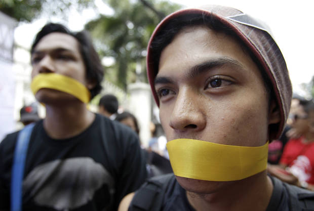 Protesters wear yellow ribbons to cover their mouths during a rally against the anti-cybercrime law in front of the Supreme Court in Manila, Philippines on Tuesday, Oct. 9, 2012. The Philippine Supreme Court on Tuesday suspended implementation of the country's anti-cybercrime law while it decides whether certain provisions violate civil liberties. (AP Photo/Aaron Favila)