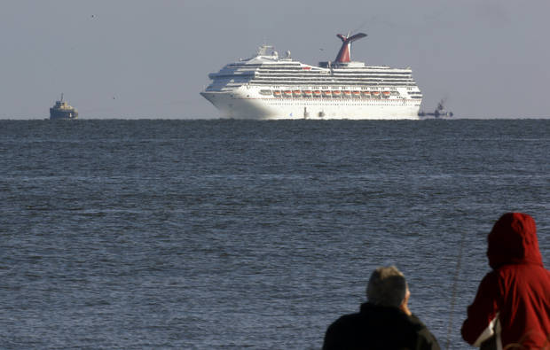 The cruise ship Carnival Triumph is towed towards Mobile Bay near Dauphin Island, Ala., Thursday, Feb. 14, 2013. The ship with over 1,000 passengers aboard has been idled for nearly a week in the Gulf of Mexico following an engine room fire. (AP Photo/Dave Martin)