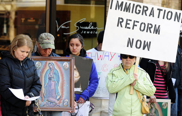 Several southwest Michigan pastors along with immigrant families and members of the general public take part in a pray-in for immigration reform event outside of Representative Fred Upton's office in downtown Kalamazoo on Friday, March 29, 2013.  (AP Photo/Kalamazoo Gazette-MLive Media Group, Matt Gade ) ALL LOCAL TV OUT; LOCAL TV INTERNET OUT