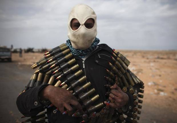 A Libyan volunteer carries ammunition on the outskirts of the eastern town of Ras Lanouf, Libya, Thursday, March 10, 2011. Government forces drove hundreds of rebels from a strategic oil port with rockets and tank shells on Thursday, significantly expanding Moammar Gadhafi's control of Libya. (AP Photo/Tara Todras-Whitehill) ORG XMIT: TTW120