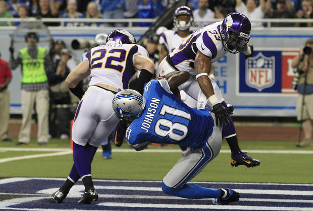 Minnesota Vikings free safety Harrison Smith (22) and strong safety Jamarca Sanford (33) break up a pass intended for Detroit Lions wide receiver Calvin Johnson (81) during the second quarter of an NFL football game at Ford Field in Detroit, Sunday, Sept. 30, 2012. (AP Photo/Carlos Osorio)
