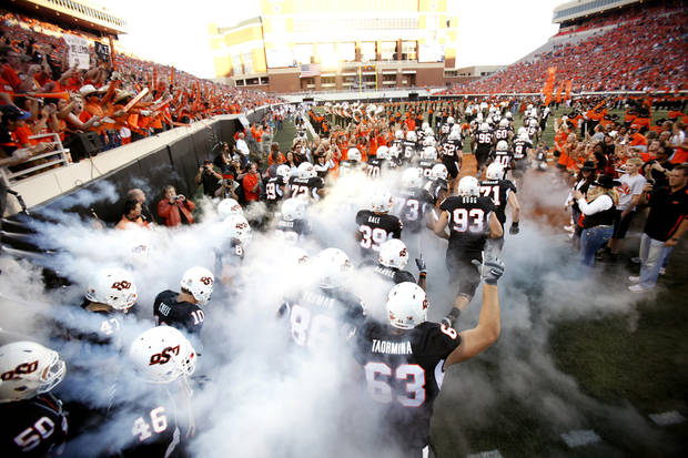 The OSU Cowboys run on the field before the college football game between Texas A&M University (TAMU) and Oklahoma State University (OSU) at Boone Pickens Stadium in Stillwater, Okla., Thursday, Sept. 30, 2010. Photo by Sarah Phipps, The Oklahoman