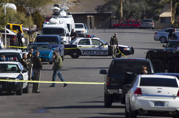 Law enforcement officials investigate a shooting and fire in Boulder City, Nev., Monday, Jan. 21, 2013. Police from several southern Nevada jurisdictions are investigating a slaying and fire at the home of a Las Vegas police lieutenant in Boulder City. (AP Photo/Las Vegas Sun, Steve Marcus)