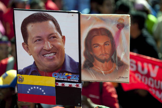 A picture of Venezuela's President Hugo Chavez is held up alongside an image of Jesus Christ at a rally by Chavez supporters in Caracas, Venezuela, Thursday, Jan. 10, 2013. The government organized the unusual show of support for the cancer-stricken leader on the streets outside Miraflores Palace on what was supposed to be his inauguration day. The Supreme Court on Wednesday backed the plan to put off the inauguration indefinitely, saying the president could be sworn in before the court at a later date. (AP Photo/Ariana Cubillos)