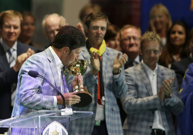 Europe's Nicolas Colsaerts and Luke Donald watch as team captain Jose Maria Olazabal kisses the trophy at the closing ceremony at the Ryder Cup PGA golf tournament Sunday, Sept. 30, 2012, at the Medinah Country Club in Medinah, Ill. (AP Photo/Chris Carlson)  ORG XMIT: PGA250