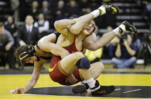 Iowa's Mike Evans tries to take down Iowa State's Tanner Weatherman during their 174-pound match in an NCAA college wrestling meet, Saturday, Dec. 1, 2012, in Iowa City, Iowa. (AP Photo/Charlie Neibergall)