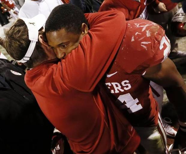 OU coach Bob Stoops, left, hugs running back Brennan Clay as the Sooners celebrate their 51-48 overtime win over OSU. Photo by Nate Billings , The Oklahoman