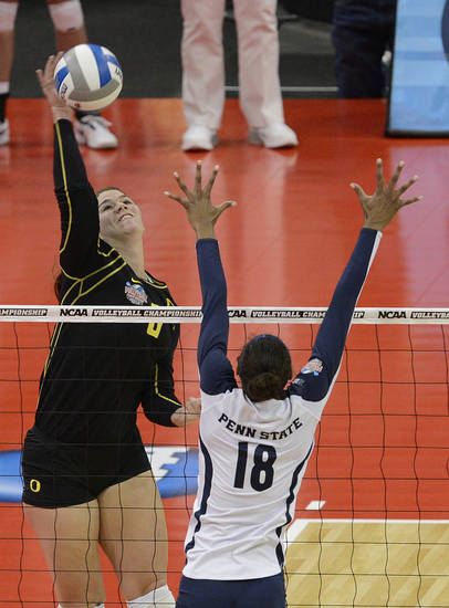 Oregon's Liz Brenner, facing, hits over the defense of Penn State's Deja McClendon during the national semifinals of the NCAA college women's volleyball tournament Thursday, Dec. 13, 2012 in Louisville, Ky. (AP Photo/Timothy D. Easley)