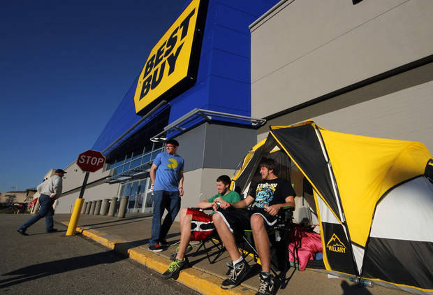 In this Nov. 21, 2012, photo, Black Friday shoppers Ryan Seech, right, Dylan Loeb, center, and Dalas Loeb, left, stake out their front of the line position at a Best Buy in West Mifflin, Pa. The Childhood friends have camped out at Best Buy for four years straight. This year, they arrived a full week early, with a tent, sleeping bags, deodorizing mist sprayer, propane heater and battery power for their gadgets. (AP Photo/Gene J. Puskar)