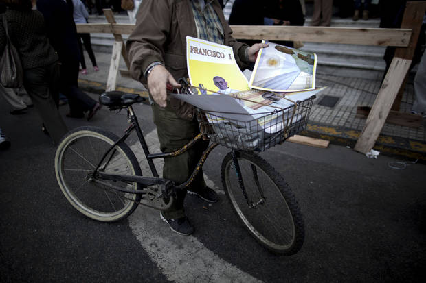 A man sells posters of Pope Francis from his bicycle outside the Metropolitan Cathedral in Buenos Aires, Argentina, Sunday, March 17, 2013.  Argentine's former cardinal Jorge Mario Bergoglio was chosen as leader of the Catholic Church on March 13, 2013. (AP Photo/Natacha Pisarenko)