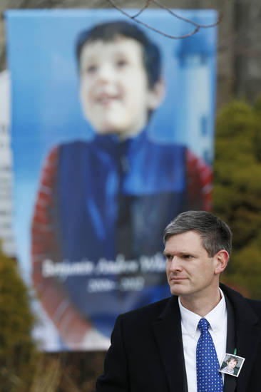 A mourner wears a photograph of Benjamin Andrew Wheeler, one of the students killed in the Sandy Hook Elementary School shooting last week, as a large portrait of Wheeler stands outside of Trinity Episcopal Church after funeral services, Thursday, Dec. 20, 2012, in Newtown, Conn. Wheeler, 6, died when the gunman, Adam Lanza, walked into Sandy Hook Elementary School in Newtown, Dec. 14, and opened fire, killing 26 people, including 20 children, before killing himself. (AP Photo/Julio Cortez)