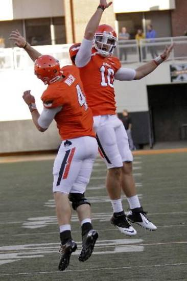 Oklahoma State's J.W. Walsh (4) and Clint Chelf (10) celebrate a touchdown during the college football game between the Oklahoma State University Cowboys (OSU) and Texas Tech University Red Raiders (TTU) at Boone Pickens Stadium on Saturday, Nov. 17, 2012, in Stillwater, Okla. Photo by Chris Landsberger, The Oklahoman