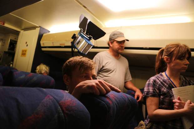 "Ryan Staples crouches behind an airliner seat to direct a scene in the film ""Skid,"" while screenwriter Rene Gutterdige, right, looks on."