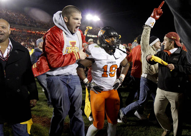 Iowa State fans rush the field past Oklahoma State's' Brodrick Brown (19) after OSU's 37-31 double-overtime loss in a college football game between the Oklahoma State University Cowboys (OSU) and the Iowa State University Cyclones (ISU) at Jack Trice Stadium in Ames, Iowa, Friday, Nov. 18, 2011. Photo by Bryan Terry, The Oklahoman
