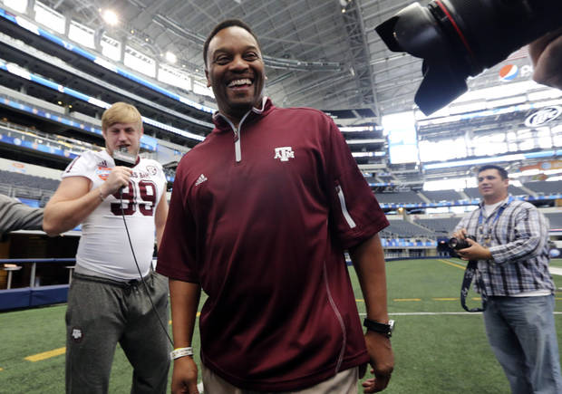 Texas A&M head coach Kevin Sumlin laughs after defensive lineman Spencer Nealy tried to interview him during media day for the Cotton Bowl NCAA college football game at Cowboys Stadium, Sunday, Dec. 30, 2012, in Arlington, Texas. Texas A&M is scheduled to play Oklahoma on Jan. 4, 2013. (AP Photo/LM Otero) ORG XMIT: TXMO111