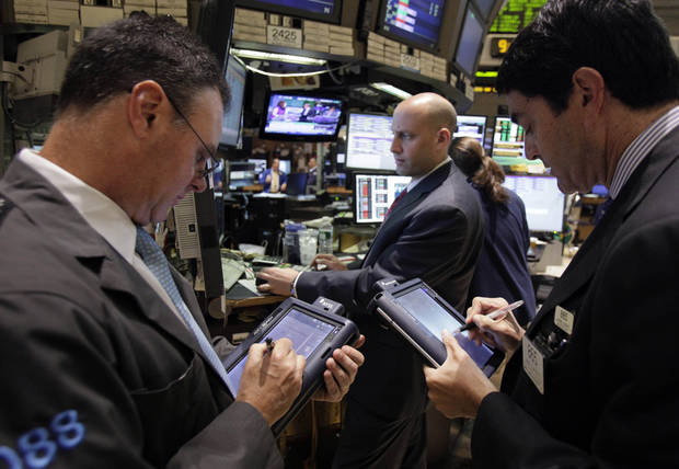 Specialist Meric Greenbaum, center, wotks at his post on the floor of the New York Stock Exchange Monday, June 18, 2012. U.S. stocks are falling after the opening bell as Europe's debt crisis roils markets despite the victory of a pro-Europe party in Greek elections. (AP Photo/Richard Drew)