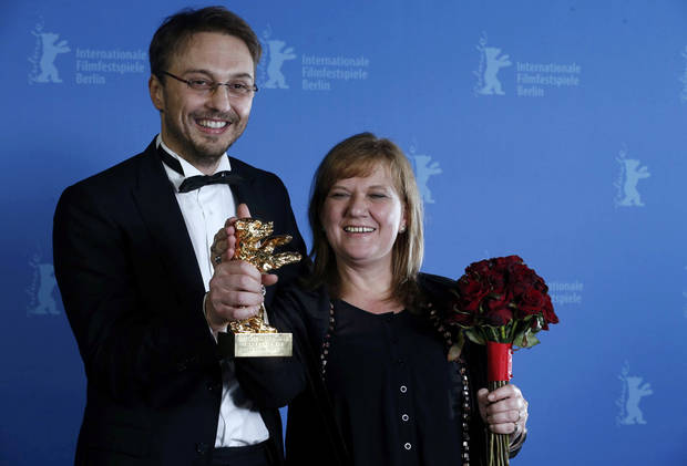 "Director Calin Peter Netzer and producer Ada Solomon pose backstage with the Golden Bear award for the Best Film for ""Pozitia Copilului"" (Child's Pose) during the awards ceremony at the 63rd Berlinale International Film Festival in Berlin Saturday, Feb. 16, 2013. (AP Photo/Thomas Peter, pool)"