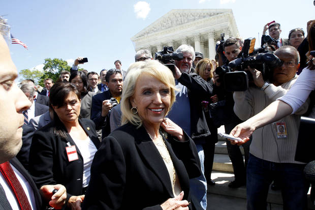 "Arizona Gov. Jan Brewer is followed by reporters outside the Supreme Court in Washington, Wednesday, April 25, 2012, after the court's hearing on Arizona's ""show me your papers"" immigration law. (AP Photo/Charles Dharapak) ORG XMIT: DCCD110"