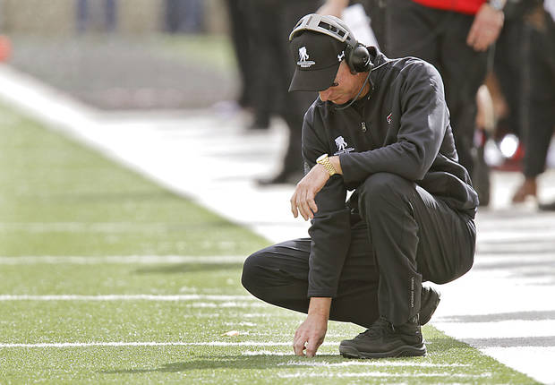 Texas Tech coach Tommy Tuberville picks at the turf in the 66-6 loss to Oklahoma State during the college football game between the Oklahoma State University Cowboys (OSU) and Texas Tech University Red Raiders (TTU) at Jones AT&T Stadium on Saturday, Nov. 12, 2011. in Lubbock, Texas.  Photo by Chris Landsberger, The Oklahoman  ORG XMIT: KOD