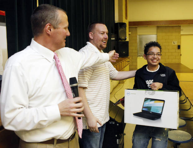 Principal Brad Herzer (left) and Assistant Principal Joey Slate hand a computer to Armando Selva as they raffle off electronics and prizes to students who attended extra Spring Break classes at Webster Middle School in Oklahoma City, OK, to catch up on their studies, Friday, March 16, 2012,  By Paul Hellstern, The Oklahoman