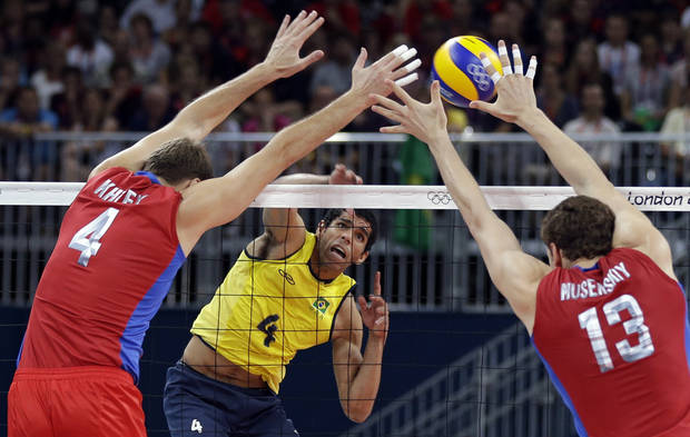Brazil's Wallace de Souza (4) spikes the ball between Russia defenders Taras Khtey (4) and Dmitriy Muserskiy (13) during a men's volleyball gold medal match at the 2012 Summer Olympics Sunday, Aug. 12, 2012, in London. (AP Photo/Chris O'Meara)