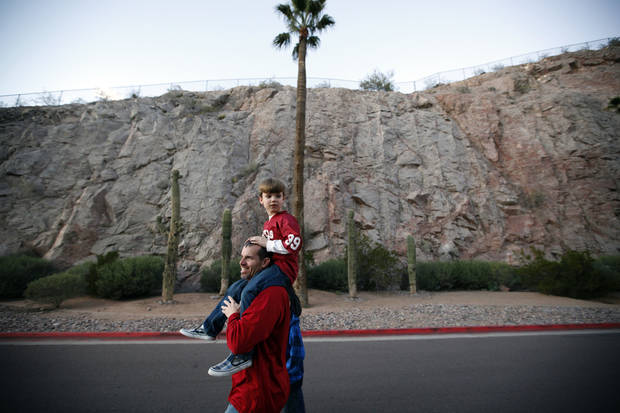 Craig Logsdon carries his son, Jude, 7, of Scottsdale, Ariz., walks toward the stadium before the Insight Bowl college football game between the University of Oklahoma (OU) Sooners and the Iowa Hawkeyes at Sun Devil Stadium in Tempe, Ariz., Friday, Dec. 30, 2011. Photo by Sarah Phipps, The Oklahoman
