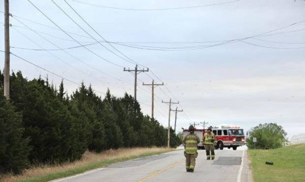Oklahoma City firemen look at power lines dislodged by high winds today on Hefner Road just east of Kelley Ave. Photo by Paul B. Southerland <strong>PAUL B. SOUTHERLAND</strong>