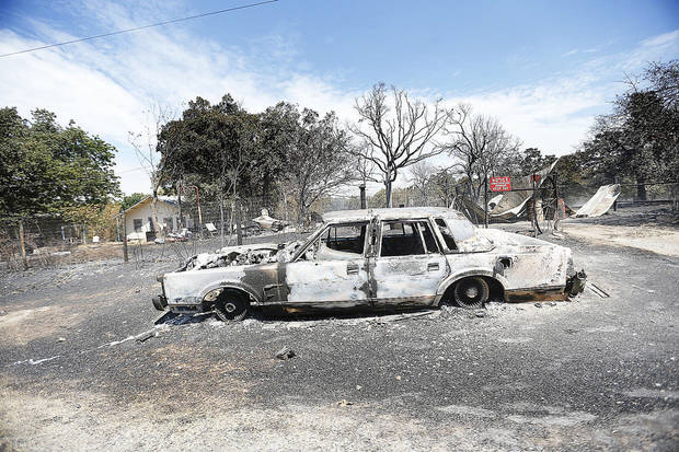 A burned car is pictured Sunday in the Oak Grove community near Drumright.