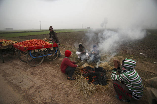 Indian vendors warm themselves near a fire in a cold and foggy morning in Jammu, India, Tuesday, Jan. 8, 2013. North India continues to face below average weather conditions with dense fog affecting flights and trains. More than 100 people have died of exposure as northern India deals with historically cold temperatures. (AP Photo/Channi Anand)