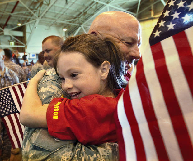 Madison Frazier, 7, hugs her grandfather, Chief Warrant Officer Benny Milam, of McLoud, as he arrives in Oklahoma City in April after being deployed to Kuwait and Afghanistan. OKLAHOMAN ARCHIVES <strong>Jim Beckel</strong>