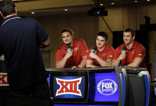 Iowa State players Cory Morrissey, right,  Jovohn Miller, center, and Tom Farniok  playfully pose for a photo at the broadcasters desk during the NCAA college Big 12 Conference football media days in Dallas, Tuesday, July 22, 2014. (AP Photo)