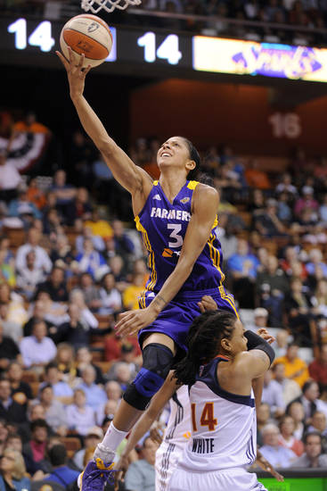 FILE - In this June 13, 2012 file photo, Los Angeles Sparks' Candace Parker, left, drives past Connecticut Sun's Tan White during the first half of a WNBA basketball game in Uncasville, Conn. The USA women's basketball team will create matchup problems at the London Games for opponents with their trio of versatile post players _ 6-foot-4 Parker, 6-6 Sylvia Fowles and 6-4 Tina Charles. Fowles dominates with her back to the basket, Charles can shoot the mid-range jump shot while Parker can take defenders off the dribble. (AP Photo/Fred Beckham, File)