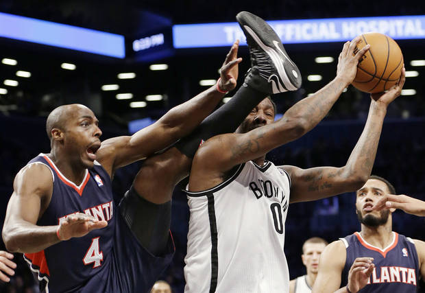 Atlanta Hawks forward Anthony Tolliver (4) tries to get the referee's attention as he becomes entangled with Brooklyn Nets forward Andray Blatche (0) in the first half of their NBA basketball game at the Barclays Center, Friday, Jan. 18, 2013, in New York. (AP Photo/Kathy Willens)