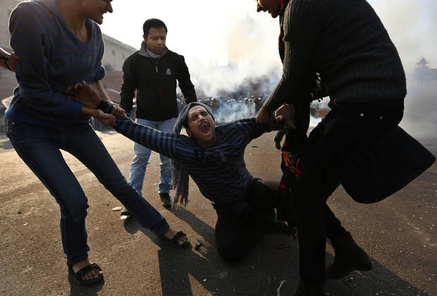 An injured man reacts,  as tear gas is fired by Indian police to drive protesters back from North Block near the Presidential Palace in New Delhi, India, Saturday, Dec. 22, 2012. Police used tear gas and water cannons to push back thousands of people who tried to march to the presidential mansion to protest the recent gang rape and brutal beating of a 23-year-old student on a moving bus. (AP Photo/Saurabh Das)