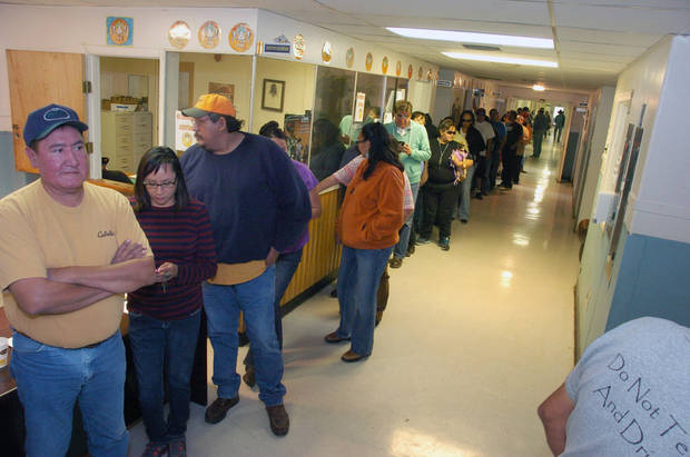 Employees of the Crow Tribe line up to receive their paychecks at the tribal offices in Crow Agency, Mont., Wednesday, Oct. 2, 2013. These are some of more than 300 tribal employees being furloughed after the federal budget impasse and government shutdown stopped payments due to the southeastern Montana tribe. (AP Photo/Matthew Brown)