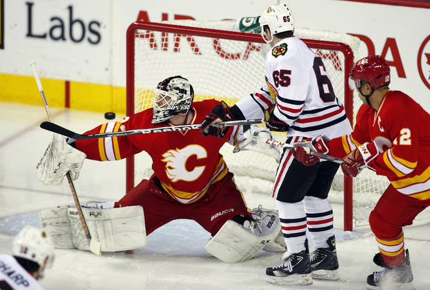 Chicago Blackhawks' Andrew Shaw, center, swats the puck past Calgary Flames goalie Miikka Kiprusoff, from Finland, during first-period NHL hockey game action in Calgary, Alberta, Saturday, Feb. 2, 2013. (AP Photo/The Canadian Press, Jeff McIntosh)
