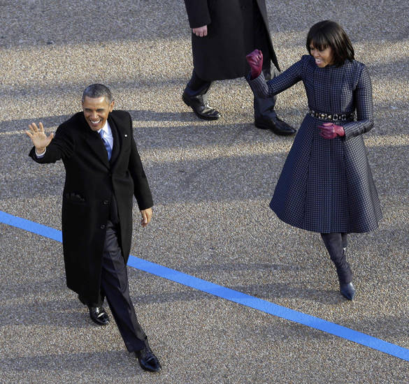 President Barack Obama and first lady Michelle Obama walk the inaugural parade route down Pennsylvania Avenue en route to the White House, Monday, Jan. 21, 2013, in Washington. Thousands  marched during the 57th Presidential Inauguration parade after the ceremonial swearing-in of President Barack Obama. (AP Photo/Charlie Neibergall)