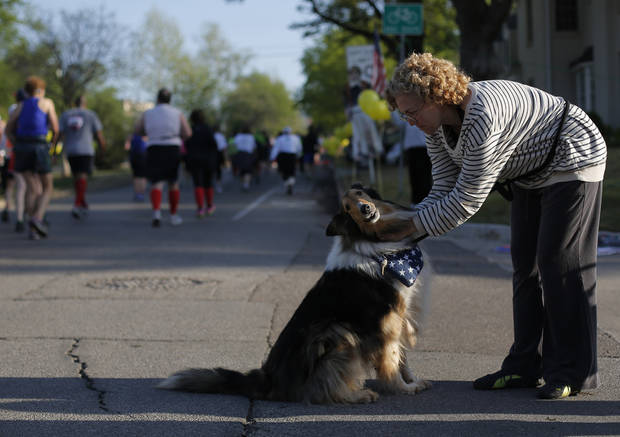 Robin Starke pets her dog, Pollie, as runners make their way up Gorilla Hill, near 39th and Shartel, during the Oklahoma City Memorial Marathon in Oklahoma City, Sunday, April 28, 2013.  Photo by Garett Fisbeck, For The Oklahoman